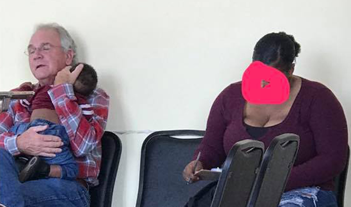 Heartwarming moment man holds sleeping baby so mom can fill out paperwork goes viral