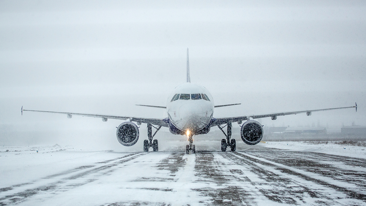 Aircraft slides off snowy runway, across field and into highway