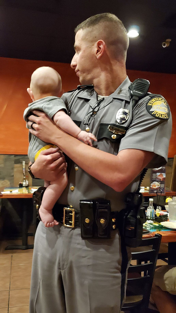 Police officer at Kentucky restaurant holds 'fussy' baby so mom can eat, viral photo shows