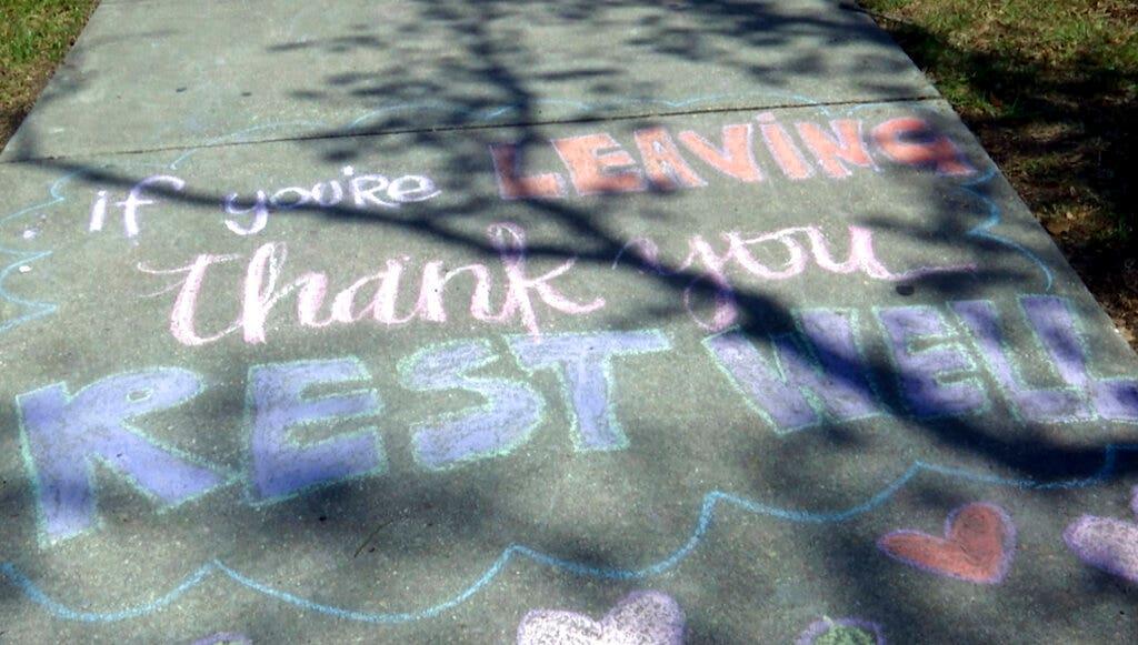 Anonim New Orleans artis daun semangat pesan di trotoar di luar rumah sakit